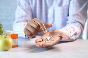 La mano del hombre con la medicina derramada fuera del recipiente de la píldora mientras se encuentra foto