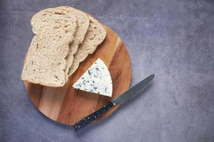 top view of blue cheese ,and slice of brown bread on table photo