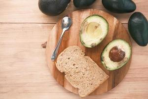Avocado on slice of a brown bread on table photo