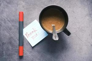 thank you message on sticky note and a coffee mug on table photo