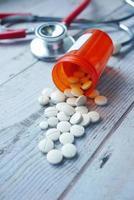 Píldoras médicas de color blanco derramándose sobre la mesa de madera foto