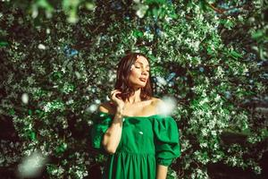 una niña está de pie en el parque debajo de un manzano en flor foto