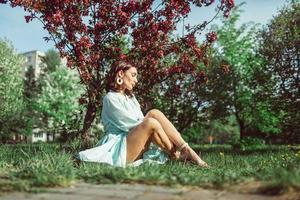 niña sentada en el parque en el césped debajo de un manzano blanco en flor foto