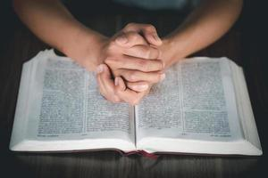 Woman hands praying to god with the Bible photo