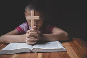 Boy hands holding a holy cross and praying to God photo