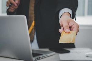 Man holding a credit card and working on laptop photo