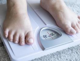 Hombre asiático pie con escalas de peso corporal para medir el peso foto