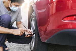 Asian man car inspection Measure quantity Inflated Rubber photo