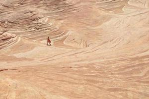 Woman walking on a sandstone rock formation in the desert photo