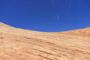 Blue sky behind a colorful sandstone rock in the desert photo