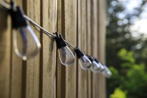 Row of lightbulbs hanging on an outdoor fence photo