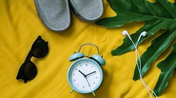 Alarm clock leaf laptop earphones on a bright yellow background photo
