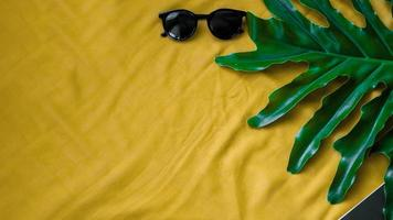 Top view leaf with glasses on yellow background photo