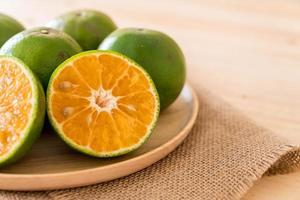 Naranja fresca en placa de madera sobre la mesa foto