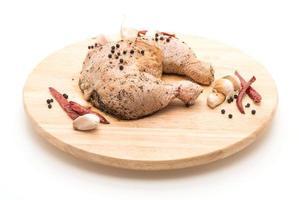 muslo de pollo marinado con salsa, pimientos negros, ajo y chile seco sobre tabla de madera foto