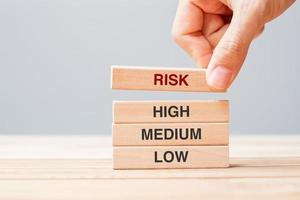 Hand pulling wooden block with Risk text photo