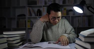 Young Man Sitting and Reading Book in Dimly Lit Library video