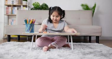 Little Girl Enjoys Drawing on Paper in Living Room video