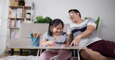 jeune père apprenant à sa petite fille à dessiner video