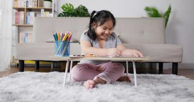 Little Girl Enjoying Drawing on A Piece of Paper in Living Room video