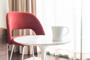 Coffee cup with beautiful luxury chair and table decoration in livingroom interior for background - Vintage Filter photo