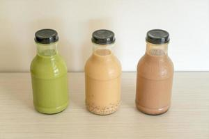 Matcha green tea latte, chocolate and milk tea with pudding jelly in a glass bottle on the table photo