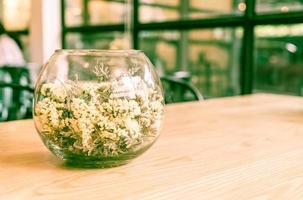 Flor en decoración de vidrio en la mesa - filtro de efecto vintage foto