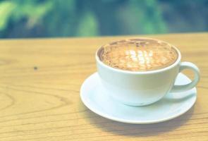 Macchiato de caramelo caliente en cafetería - filtro de efecto vintage foto