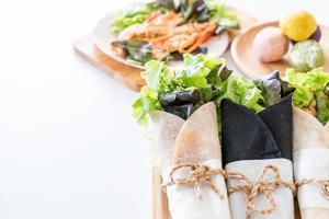 envuelva el rollo de ensalada en la mesa foto