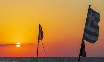 banderas en la más hermosa puesta de sol playa de ialysos rodas grecia. foto