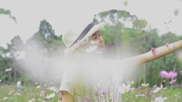 Cute girl taking selfie portrait among beautiful cosmos flower field. video