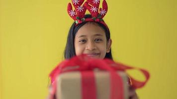 Girl in red sweater wears reindeer antlers headband giving a gift box. video