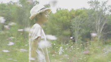 fille heureuse marchant dans le champ de fleurs de cosmos au printemps. video