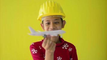 linda garota usa capacete de segurança no suéter vermelho, brincando com o brinquedo do avião. video