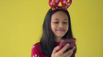 Girl in red sweater listening music from mobile phone with earphones. video