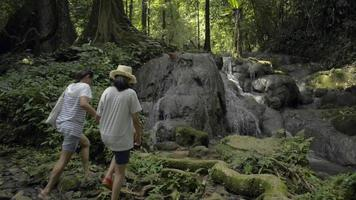 mère et sa fille marchant pour voir la cascade dans la forêt tropicale. video