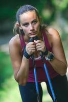 Joven mujer deportiva con bastones de marcha nórdica está descansando foto