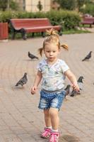 Little girl toddler runs after pigeons. Summertime photo