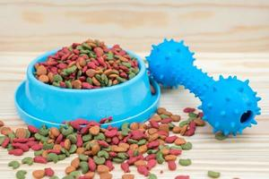 Rubber toy and dry food for pet on wooden background photo