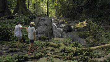 mère et fille marchant pour voir la cascade dans la forêt tropicale. video