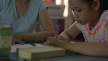 Cute girl listening her mom doing homework on the desk in living room. video