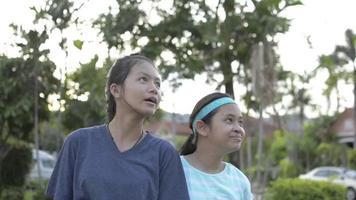 deux jolies filles regardant un grand arbre dans un parc public. video