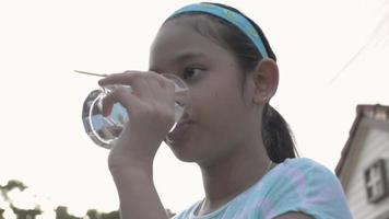 Healthy cute girl holding a glass and drink water after exercise. video