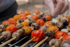 Chicken hearts with tomato and onion cooking on hot grill photo
