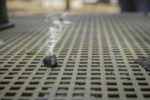 Smoke emitted from a piece of burnt wood coal on a metal table photo