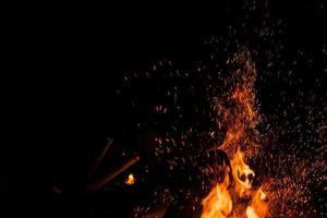 Sparks bounce off from a bonfire at night after a log thrown into it photo