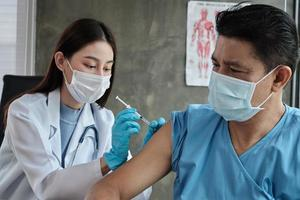 Doctor vaccinating male Asian patient to protect COVID19. photo