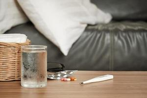 Capsule pills, medicines, thermometer, water, and tissues on a table. photo