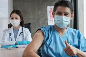 Asian male patient with face mask thumb up with a female doctor. photo