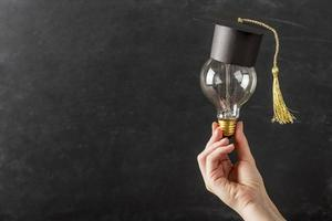 person holding light bulb with graduation cap. photo